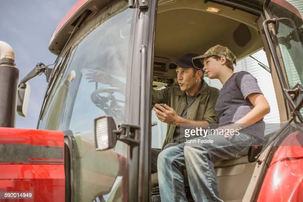 Caucasian farmer teaching son to drive tractor