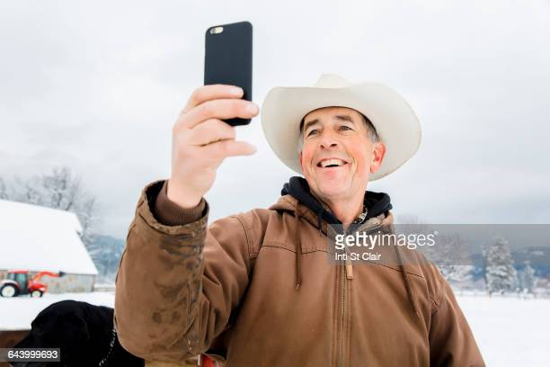 Caucasian farmer using cell phone in snowy field