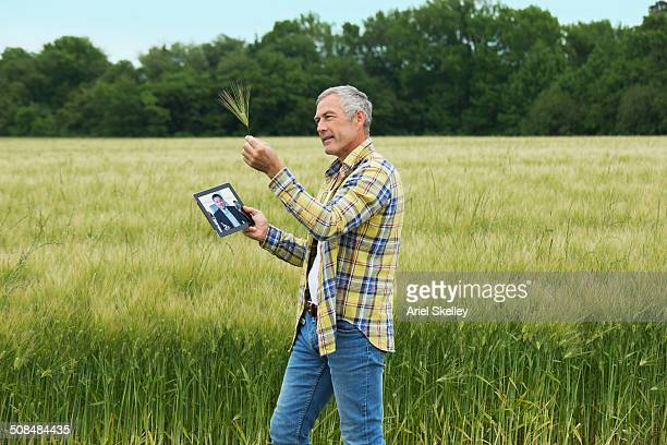 Caucasian farmer video chatting with businessman
