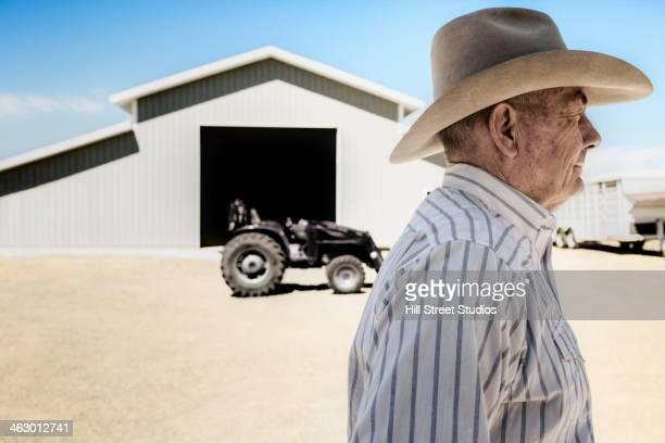 Caucasian farmer walking past barn