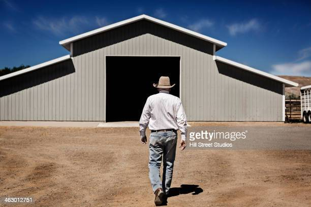 Caucasian farmer walking to barn