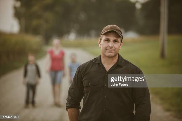 Caucasian farmer with family on dirt road