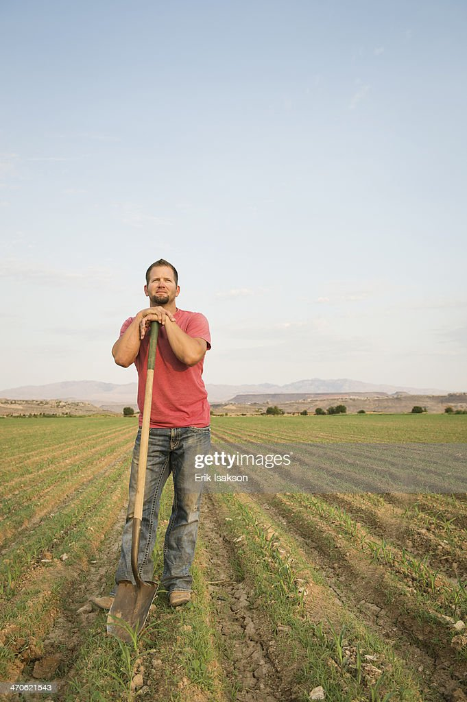 Caucasian farmer with shovel in crop field