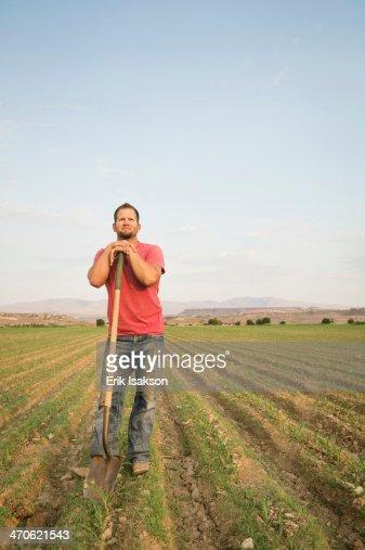 Caucasian farmer with shovel in crop field