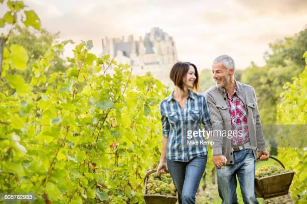 Caucasian farmers carrying grapes in vineyard