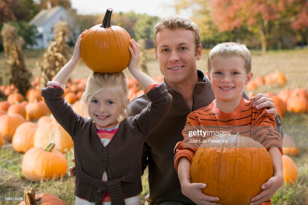 Caucasian father and children holding pumpkins : Stock Photo