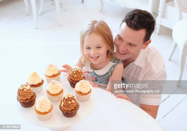 Caucasian father and daughter admiring tray of cupcakes