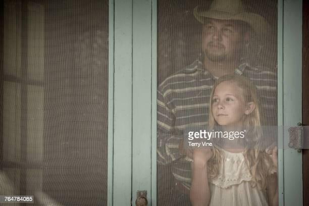 Caucasian father and daughter behind screen door