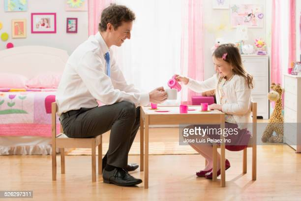 Caucasian father and daughter having tea party in bedroom