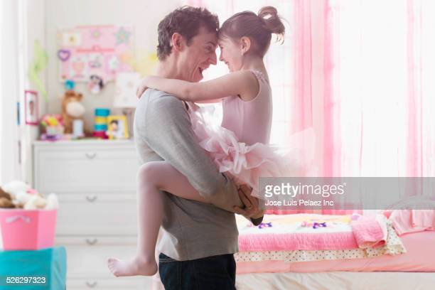 Caucasian father and daughter hugging in bedroom