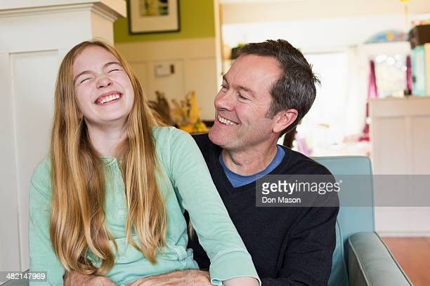 Caucasian father and daughter laughing in living room