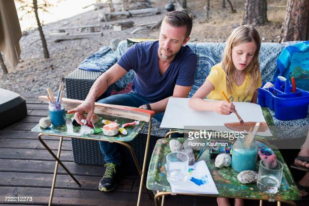Caucasian father and daughter painting on paper outdoors