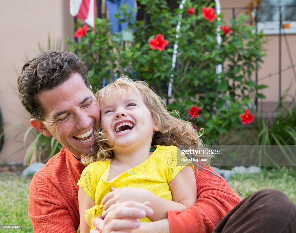 Caucasian father and daughter playing in backyard