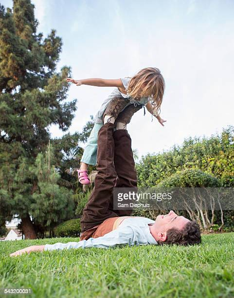 Caucasian father and daughter playing in grass