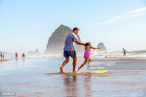 Caucasian father and daughter playing in surf on beach
