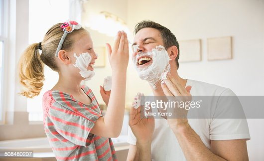 Caucasian father and daughter playing with shaving cream