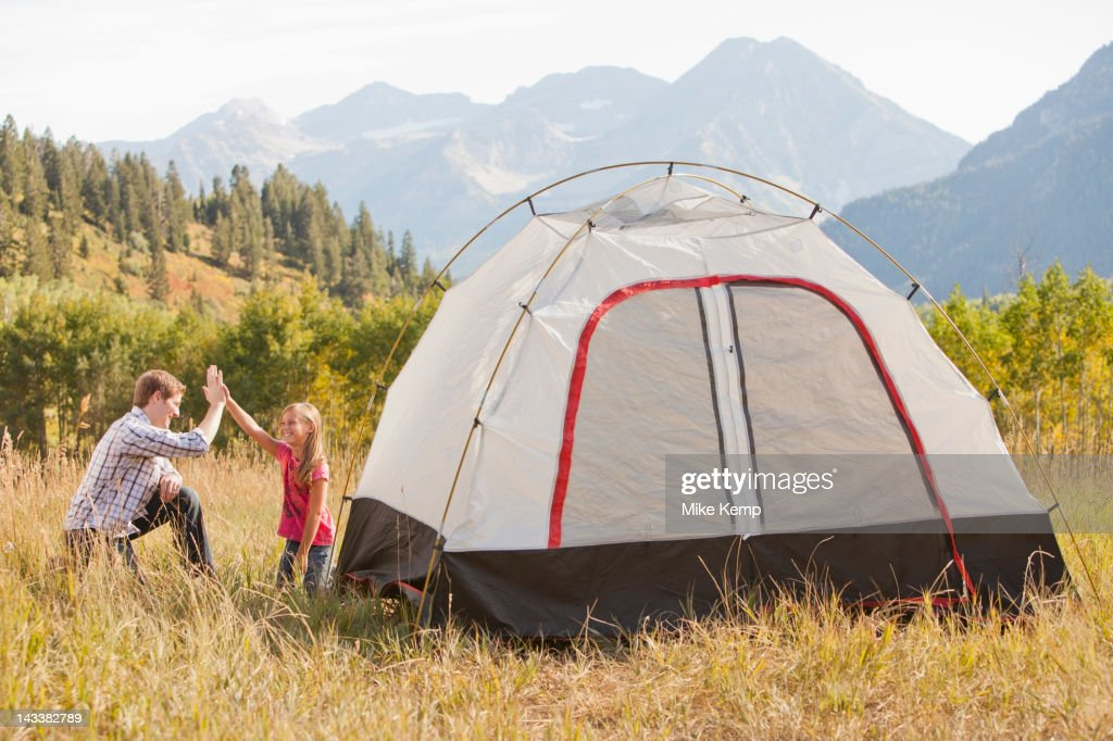 Caucasian father and daughter setting up tent : Stock Photo