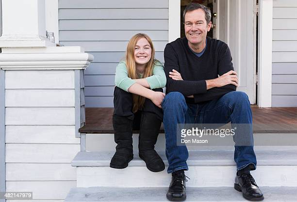 Caucasian father and daughter smiling on steps