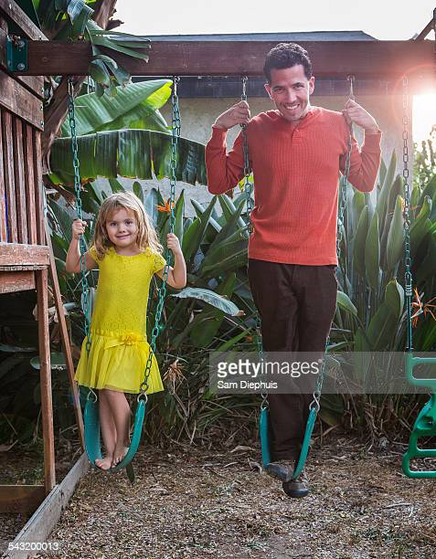 Caucasian father and daughter standing on swings