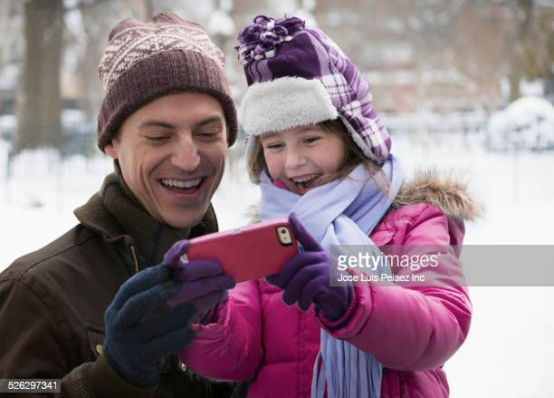 Caucasian father and daughter using cell phone in snow