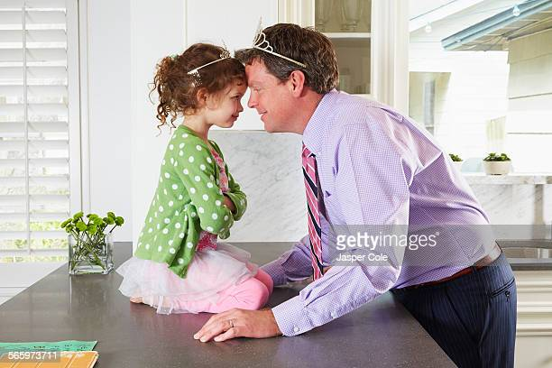 Caucasian father and daughter wearing tiaras in kitchen