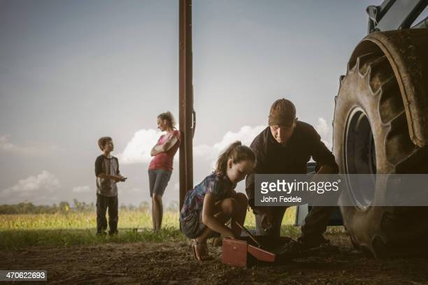 Caucasian father and daughter working on tractor