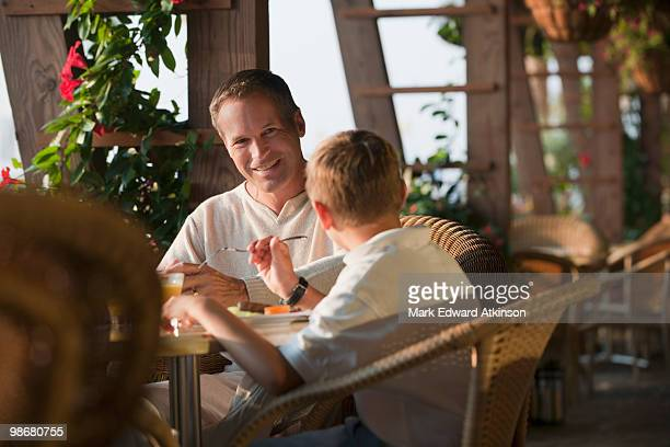 Caucasian father and son eating in restaurant