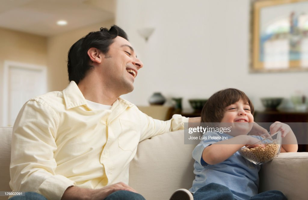 Caucasian father and son eating snack on sofa : Stock Photo