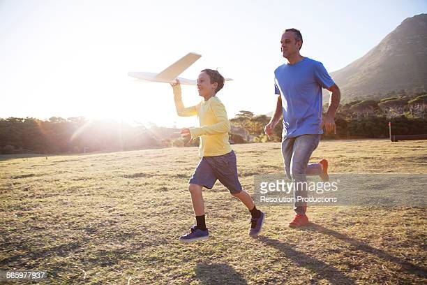 Caucasian father and son flying model airplane in field