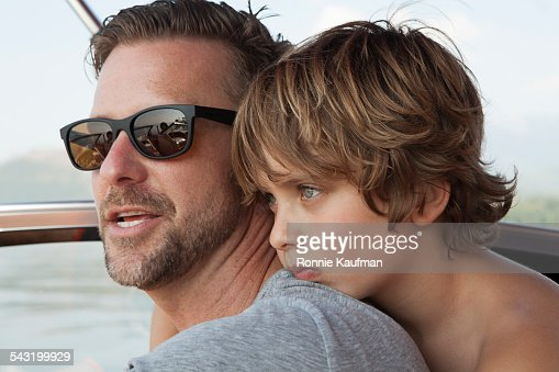 Caucasian father and son hugging outdoors