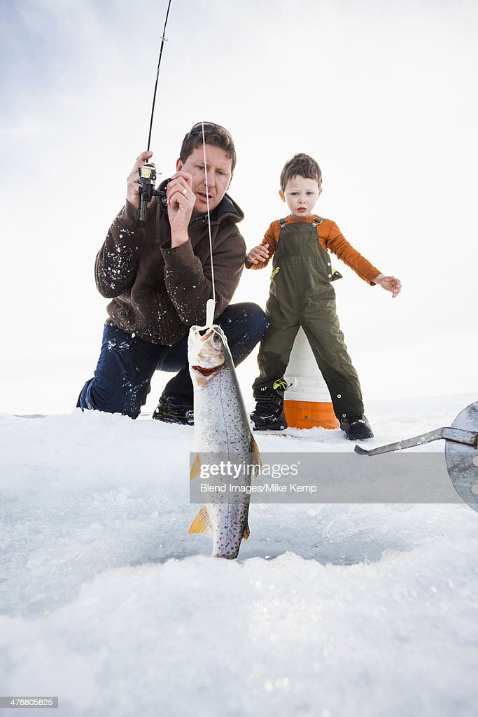 Caucasian father and son ice fishing : Stock Photo