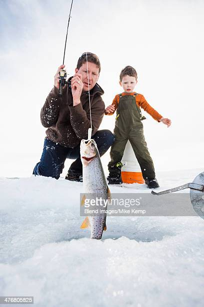 Caucasian father and son ice fishing