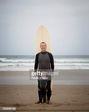 Caucasian father and son in wetsuits with surfboard : Stock Photo