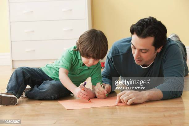 Caucasian father and son laying on floor drawing