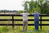Caucasian father and son leaning on fence by rural field