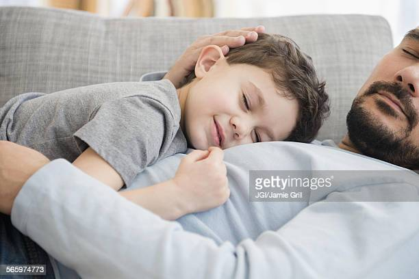 Caucasian father and son napping on sofa