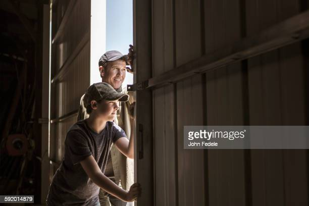 Caucasian father and son opening barn door