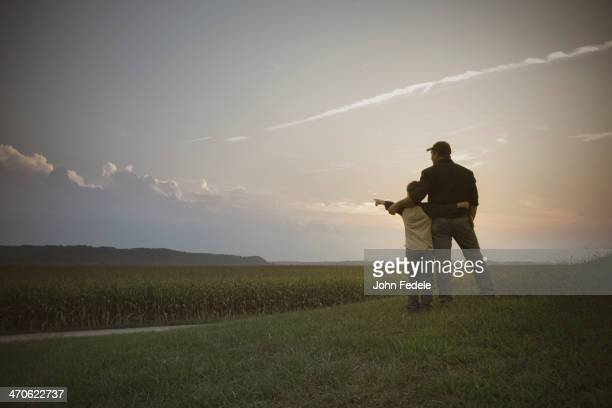 Caucasian father and son overlooking crop fields