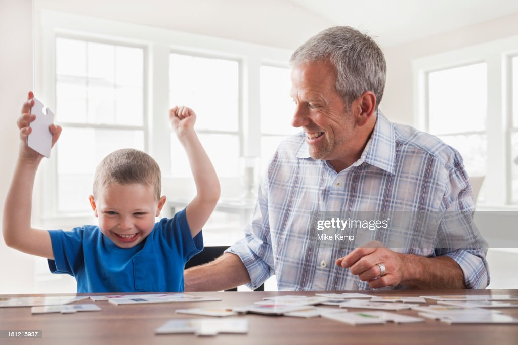 Caucasian father and son playing cards : Stock Photo
