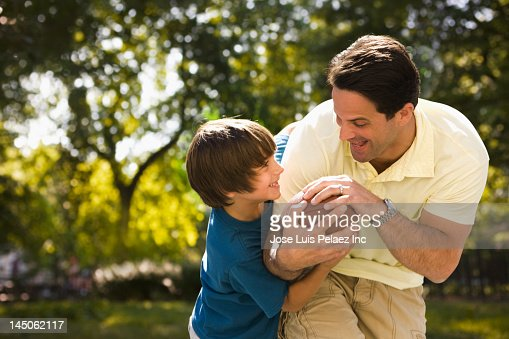 Caucasian father and son playing football : Stock Photo