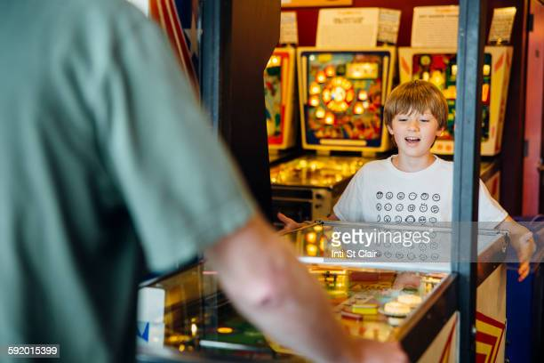Caucasian father and son playing game in arcade