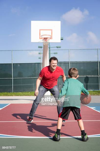 Caucasian father and son playing on basketball court