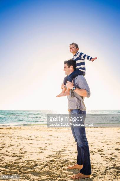Caucasian father and son playing on beach