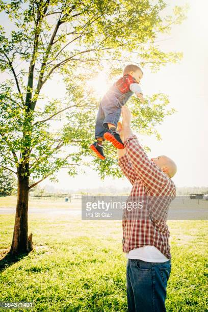 Caucasian father and son playing on farm