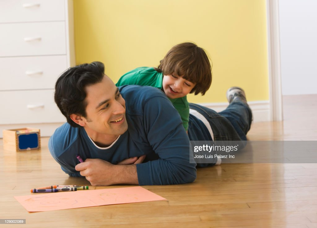 Caucasian father and son playing on floor : Stock Photo