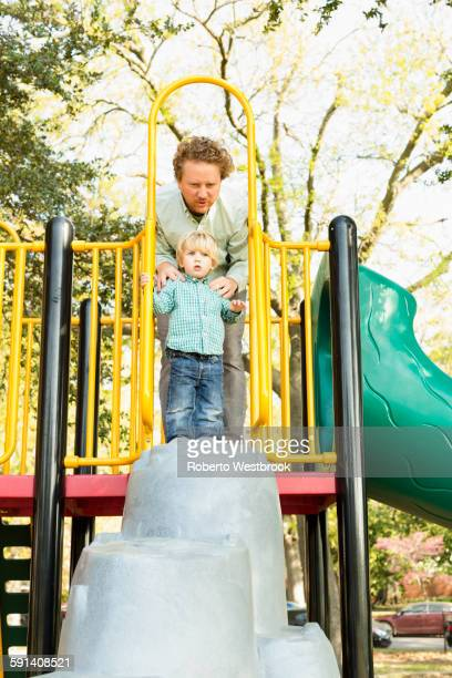 Caucasian father and son playing on play structure