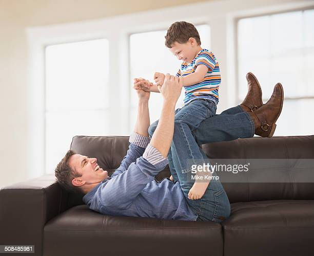 Caucasian father and son playing on sofa