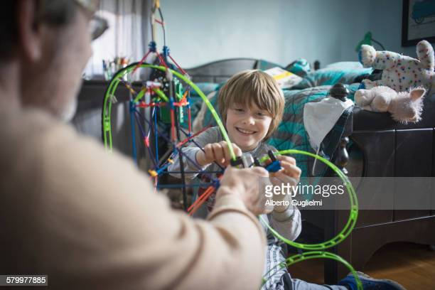 Caucasian father and son playing with toys in bedroom