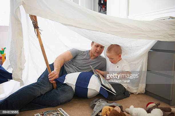 Caucasian father and son reading in blanket fort