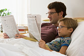 Caucasian father and son reading newspapers in bed